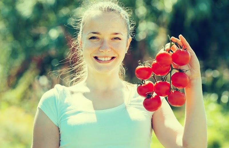 Uśmiechnięta kobieta z gałązką pomidorów