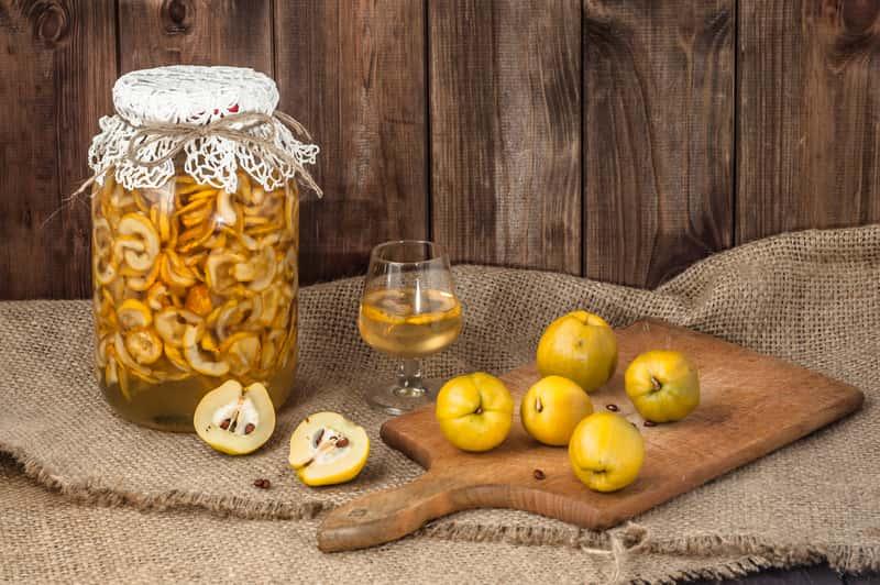 Syrop z pigwy przygotowywany w dużym słoju oraz owoce pigwy i syrop pigwowy w kieliszku