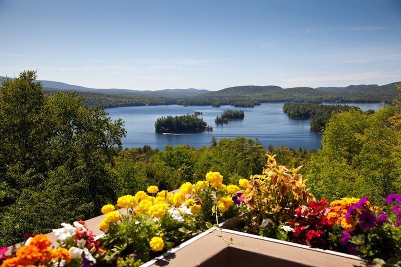Ukwiecony balkon na tle jeziora, a także informacje, jakie kwiaty na balkon sprawdzają się najlepiej, idealneg gatunki i odmiany na balkon