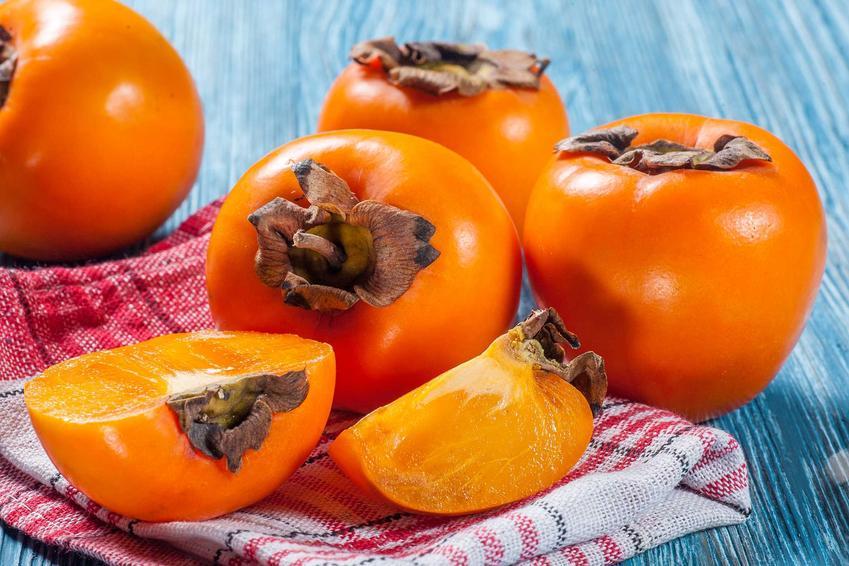Owoce kaki leżące na ściereczce, a także uprawa doniczkowa w Polsce owoców kaki krok po kroku, zastosowanie, sadzenie, pielęgnacja
