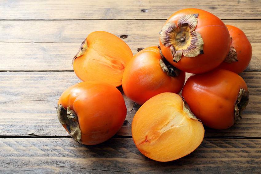 Owoce kaki na drewnianym stole, a także najważniejsze informacje, sadzenie w doniczkach, uprawa i pielęgnacja krok po kroku