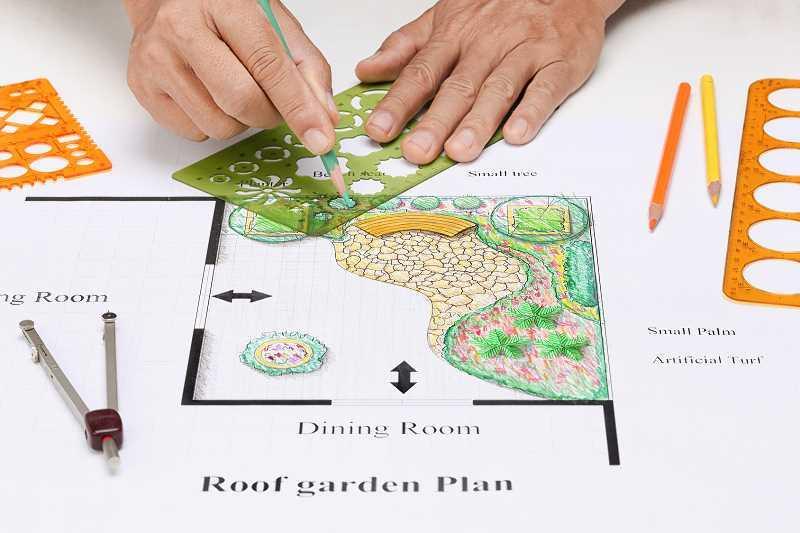 Osoba projektująca ogród ręcznie, a także cenniki projektowania ogrodów na terenie całej Polski krok po kroku