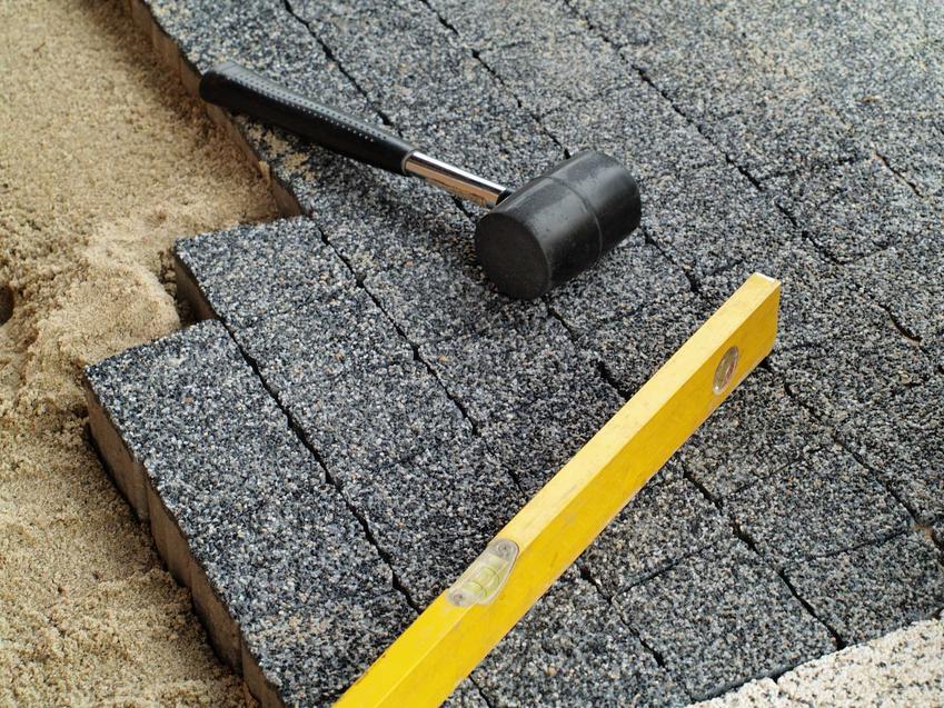 Kostka granitowa - układanie na przygotowanej powierzchni, zestaw kostek ze specjalistycznym młotkiem i poziomicą