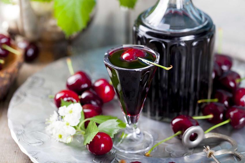 Nalewka z czereśni na spirytusie w ozdobnym kieluszku na nóżce i szklanej karafce na okrągłej tacy w otoczeniu dojrzałych owocow czereśni