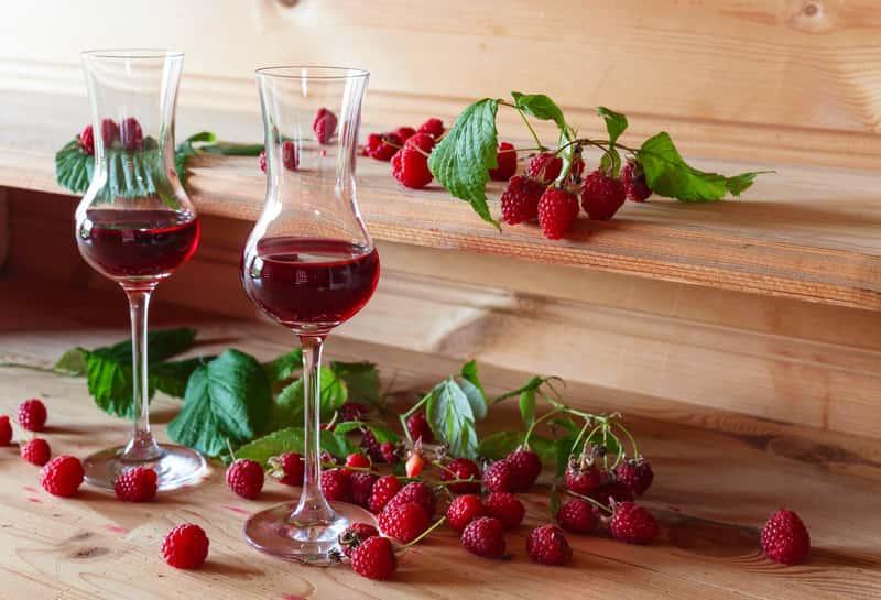 Wino z malin w szklanej butelce i maliny, a także porady, jak zrobić najlepsze wino z malin i sprawdzone przepisy