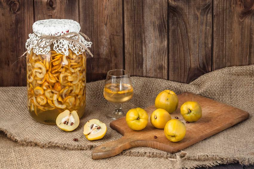 Syrop z pigwy przygotowywany w dużym słoju oraz owoce pigwy i syrop pigwowy w kieliszku, a także właściwości, zastosowanie i przepisy