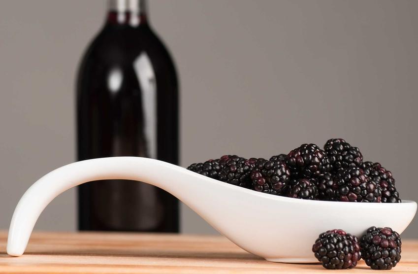 Wino z jeżyn w butelce i jeżyny na pierwszym planie. Wino jeżynowe w domu krok po kroku, najlepsze receptury i przepisy