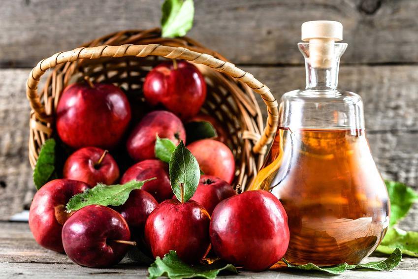 Wino z jabłek obok czerwonych owoców jabłek oraz najlepszy przepis na domowe wino z jabłek krok po kroku