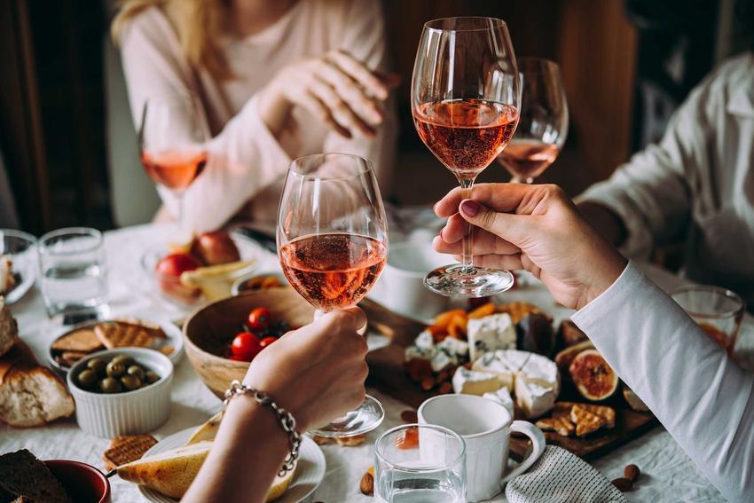 Biesiadnicy przy stole pijący wino z dzikiej róży oraz najlepsze przepisy na wino z róży krok po kroku