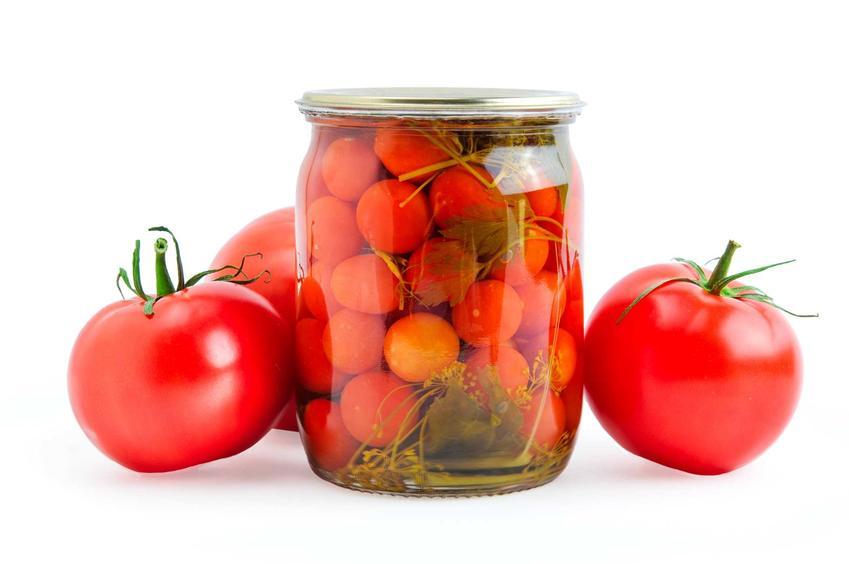 Pomidorki koktajlowe w zalewie octowej jako prztwory na zimę w słoiku oraz świeże pomidory obok