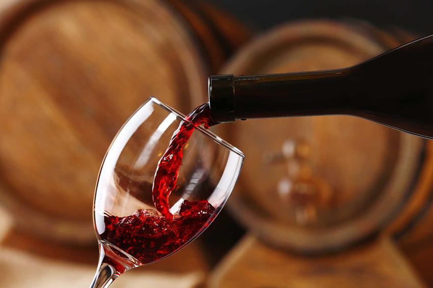 Wino z truskawek przelewane do kieliszka na tle drewnianych beczek oraz przepis na wino truskawkowe