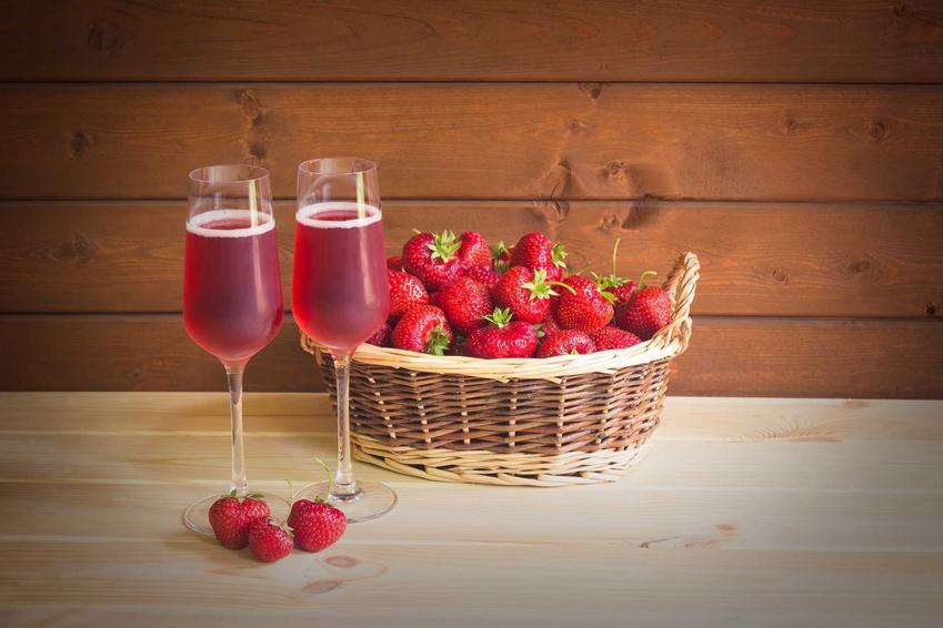 Wino z truskawek w kieliszkach oraz koszyk świeżych truskawek, a także przepis na wino truskawkowe