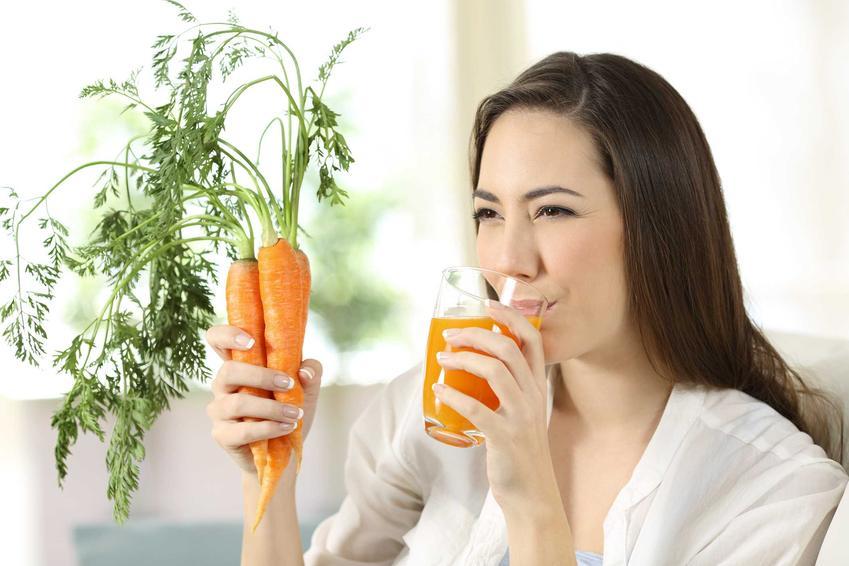 Kobieta pijąca sok z marchwi i trzymająca marchew, a także sok marchewkowy i jego właściwości, działanie oraz zastosowanie