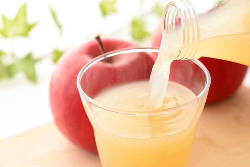 Sok jabłkowy jako świeży sok przelewany z butelki do szklanki oraz wyciskanie soku i jego właściwości