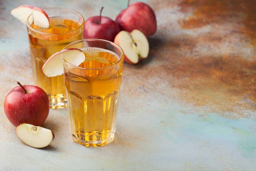 Sok jabłkowy w szklance oraz świeże jabłka, a także jego właściwości i wyciskanie soku z jabłek krok po kroku