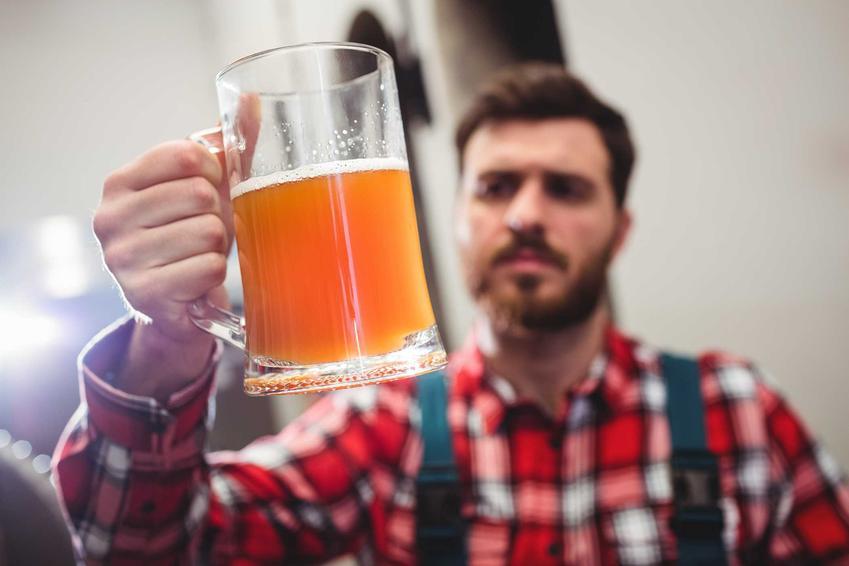 Mężczyzna oceniający proces produkcji piwa oraz szczegółowo opisana produkcja piwa w domu krok po kroku