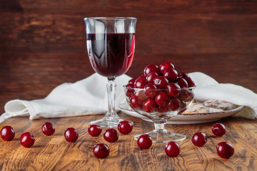 Wino z wiśni w kieliszku oraz świeże wiśnie, a także wino wiśniowe i porady, jak zrobić wino z wiśni