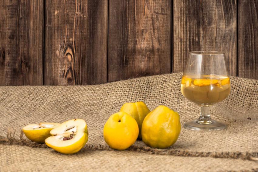 Domowe wino z pigwy w kieliszku oraz świeże owoce z pigwowca oraz wino z pigwowca i różniźe między nimi
