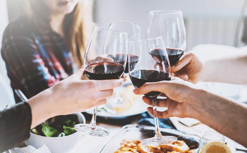 Znajomi przy stole z kieliszkami wina oraz przepis na wino z czeremchy krok po kroku, składniki i wykonanie