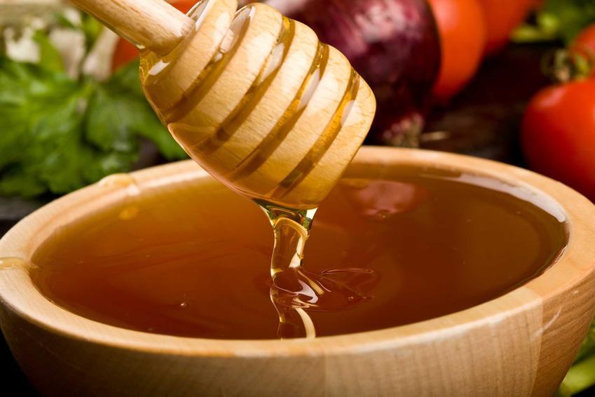 Miód na drewnianej łyżeczce i syrop z cebuli i miodu oraz przepis jak zrobić syrop z cebuli i miodu krok po kroku