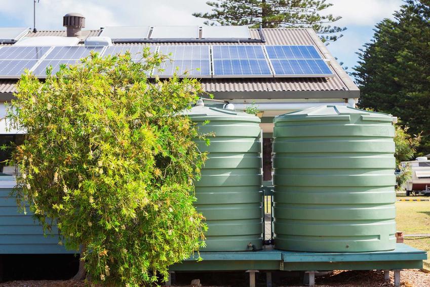 Duży zbiornik na deszczówkę oraz deszczówka zmagazynowana w pojemnikach, a także polecany pojemnik na deszczówkę do ogrodu