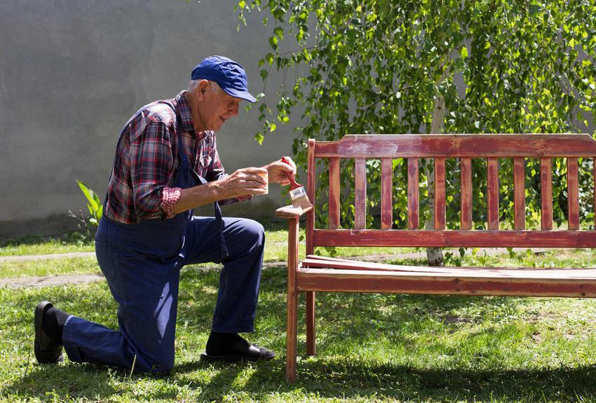 Drewniana ławeczka ogrodowa podczas malowania oraz porady, jak zrobić ławkę ogrodową, ciekawe rozwiązania i kompozycje - krok po kroku