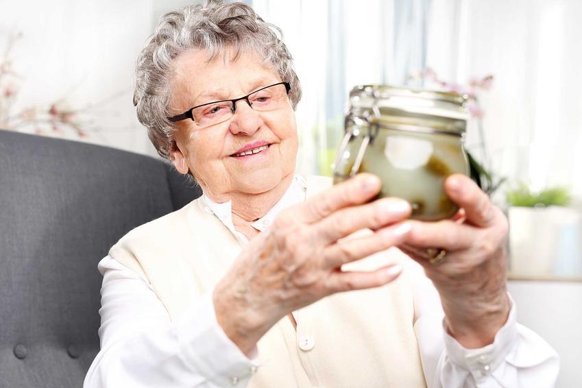 Starsza pani trzymająca słoik ogórków, a także sok z kiszonych ogórków, jego właściwości lecznicze i wpływ na zdrowie układu pokarmowego