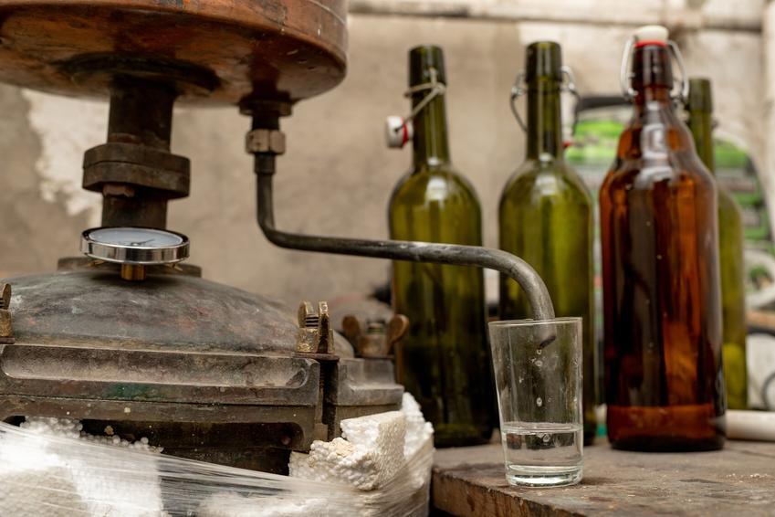 Produkacja bimbru i butelki w tle, a także samogon lub bimber a przepisy prawne