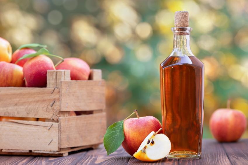 Cydr jabłkowy w butelce oraz skrzynka z jabłkami, a także przepis jak ztobić cydr jabłkowy