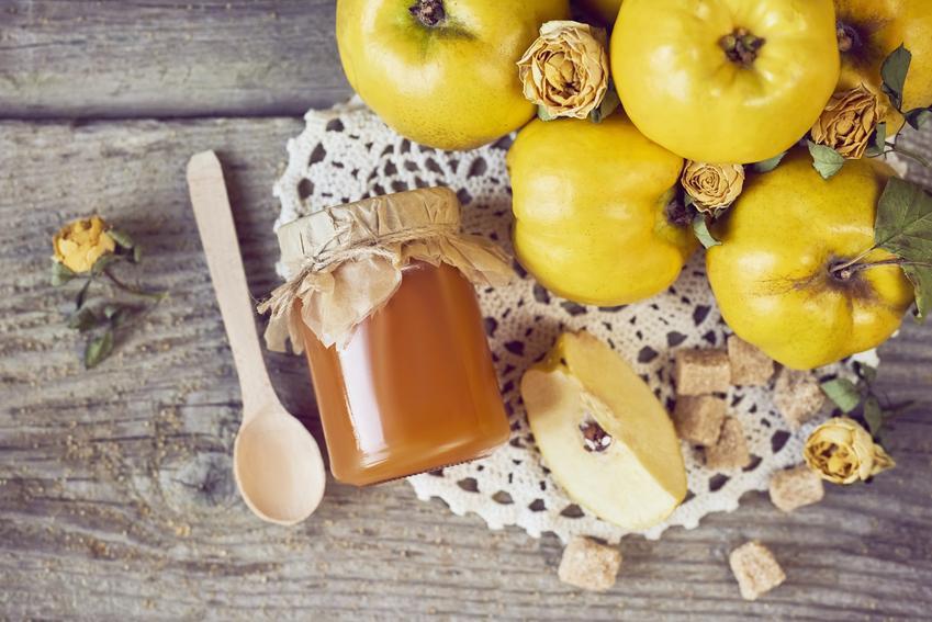 Konfitura z pigwy do herbaty na drewnianym stole oraz owoce pigwy, a także przepisy na przetwory