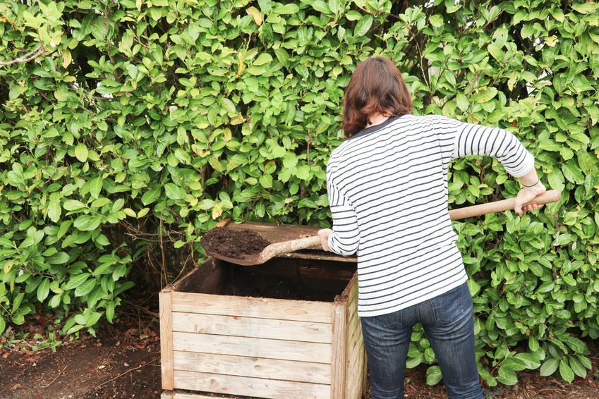 Kobieta przy kompostowniku, a także, czym jest kompost i na czym polega kompostowanie