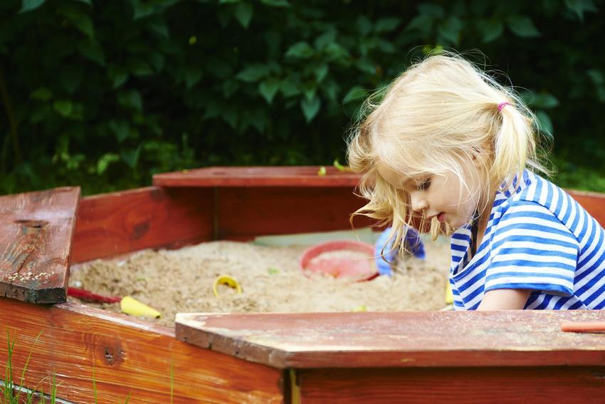 Dziewczynka bawiąca się w piaskownicy, a także piaskownica dla dzieci i zamykane piaskownice