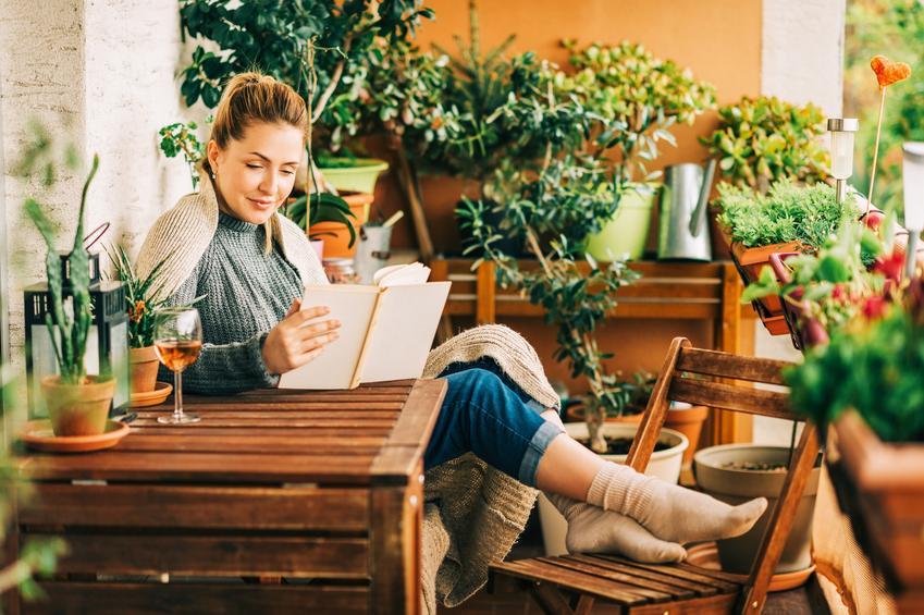 Kobieta siedząca na balkonie wśród kwiatów oraz jak zaprojektować ogród na balkonie