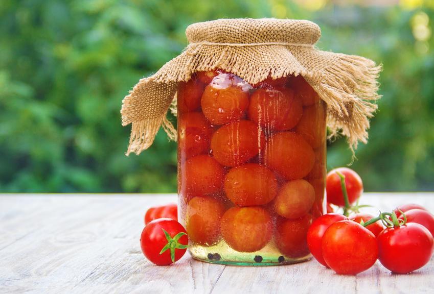 Pomidory kiszone w słoiku na tle zieleni, a także przepis na kiszone pomidory po rosyjsku