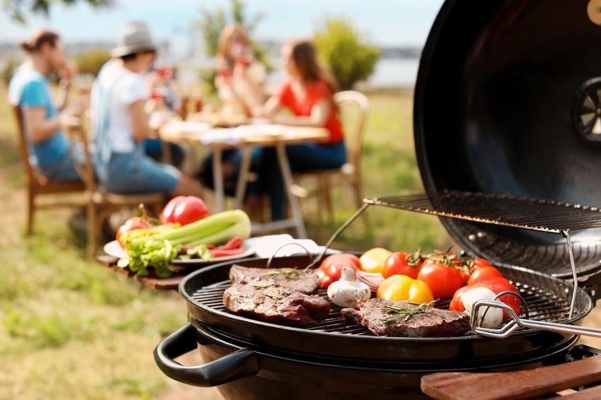Grill w ogrodzie i znajomi przy stole w tle, a także dania z grilla, potrawy z grilla, przepisy na grilla