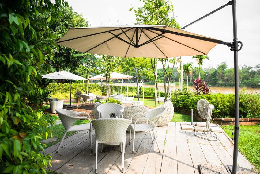Parasol ogrodowy w pięknym ogrodzie, a także polecane w sklepach parasole ogrodowe