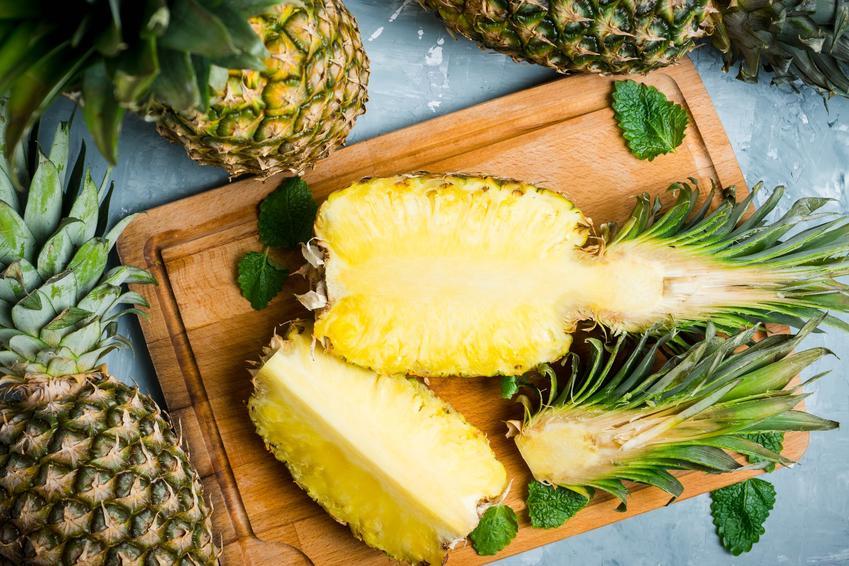 Ananas przekrojony na drewnianej desce, a także właściwości zdrowotne, witaminy