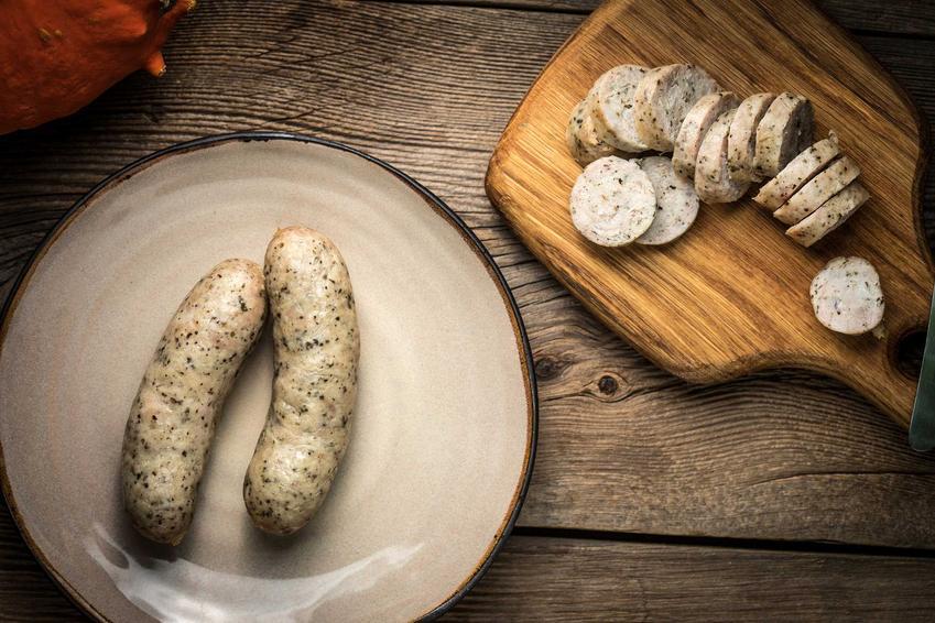 Biała kiełbasa w sosie chrzanowym gotowana na desce do krojenia, a także przepis na przygotowanie dania