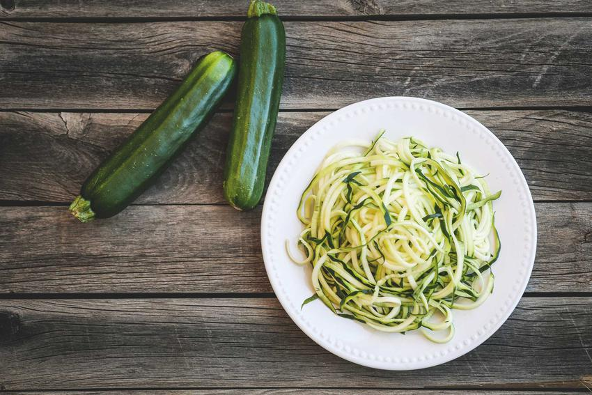Spaghetti carbonara z cukinią i dodatkami na talerzu, a także przepisy i jak przygotować karbonarę