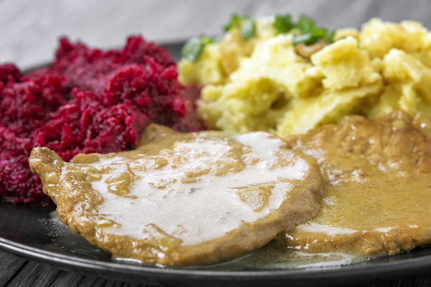 Szynka w sosie własnym na ciemnym talerzu z ziemniakami i buraczkami, a także przepisy oraz składniki