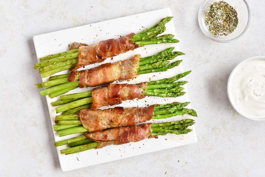 Szparagi zawinięte w boczku i upieczone w piekarniku na białym talerzyku z ziołami, a także przepisy i sposób podania