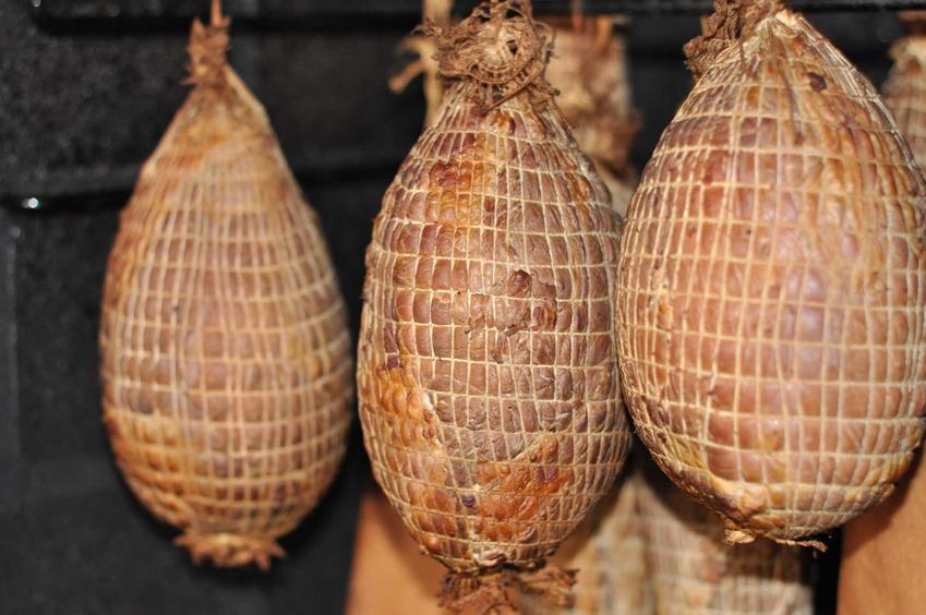 Szynka przygotowana do wędzenia wisząca w wędzarce w woreczkach, a także porady i przepisy dotyczące wędzenia mięsa