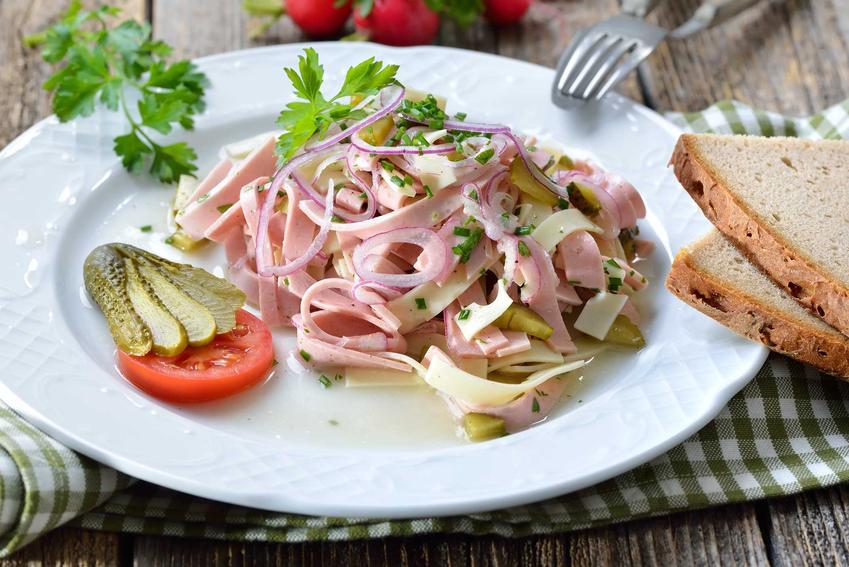 Sałatka szwajcarska z serem i szynką na białym talerzu podana z chlebem, a także przepisy, wykonanie, najlepsze porady