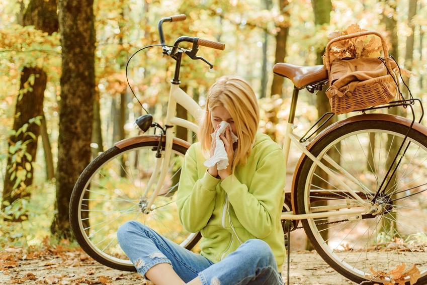 Kobieta siedząca w lesie i wycierająca nos z powodu alergii na pyłki, a także co aktualnie pyli krok po kroku