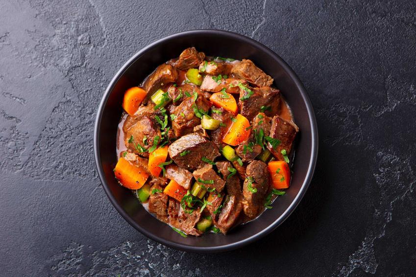Gulasz z dzika z warzywami w czarnej miseczce, a także TOP 5 najlepsze przepisy na gulasz z mięsa dzika