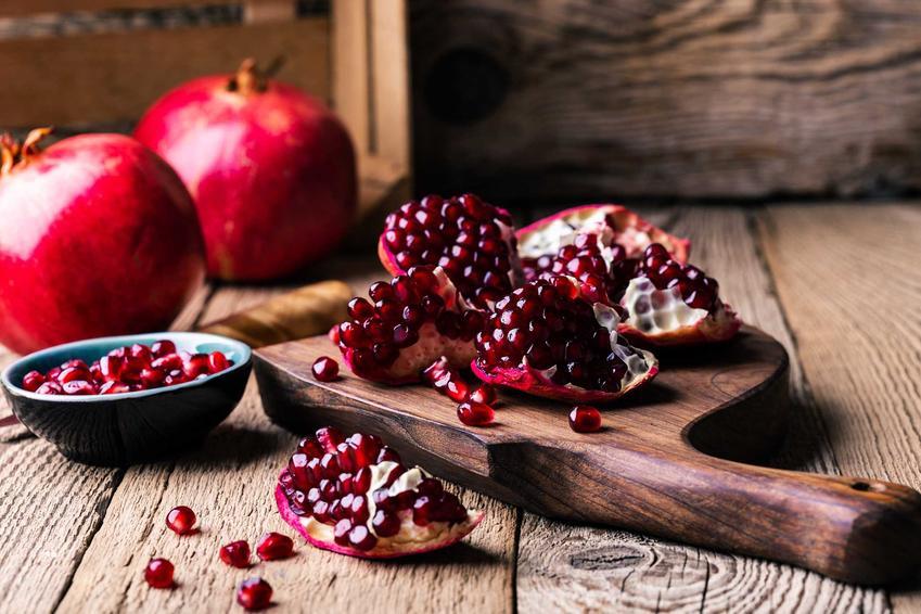 Owoce granatu na stole i desce do krojenia, a także opis, występowanie, zastosowanie i właściwości oraz sok z granatu