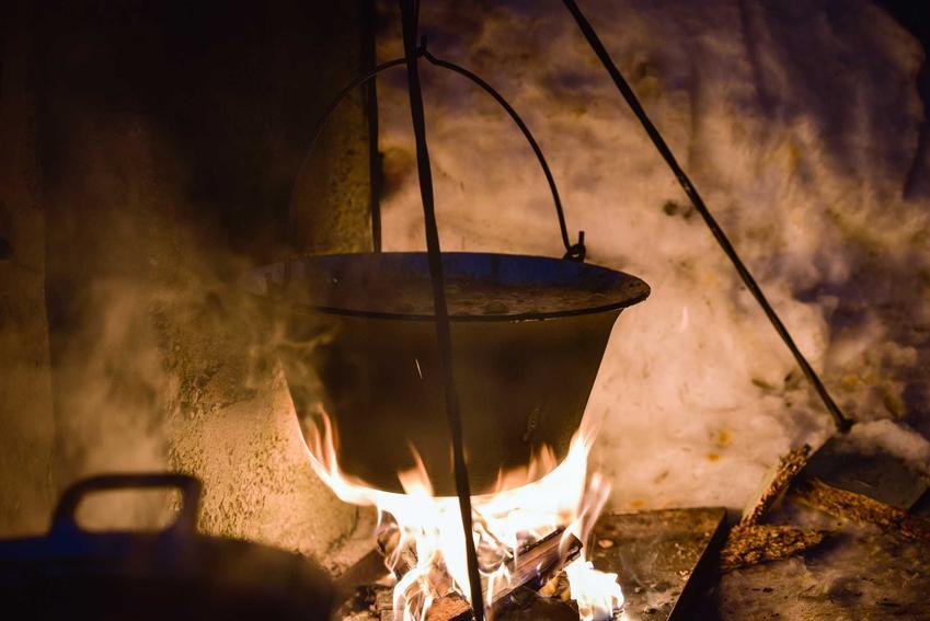 Kociołek myśliwski z gotującą się zupą na ognisku, a także rodzaje kociołków, cena, sposób użycia oraz opinie