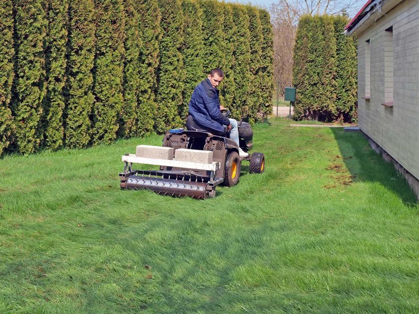 Mężczyzna siedzi na dużym aeartorze, ogrodnik napowietrza trawnik, zabieg aeracji i wertykulacji niezbędne do utrzymania trawnika