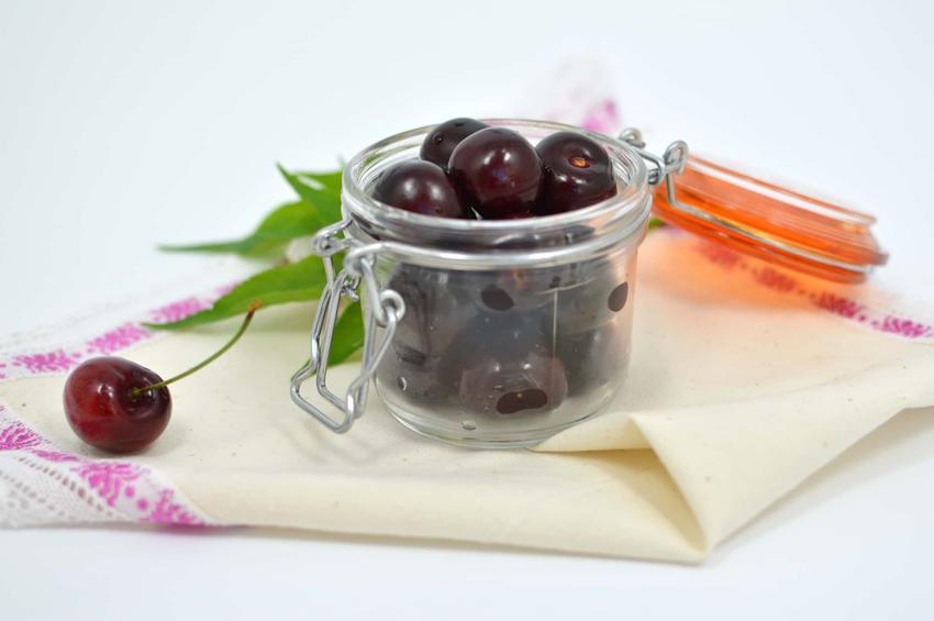 Słoik z czereśniami leżący na blacie, przepis na karmelizowane czereśnie, przepis na kompot z czereśni