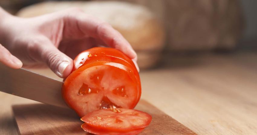 Pomidor na desce drewnianej podczas krojenia nożem, a także informacje, jakie są właściwości odżywcze pomidorów